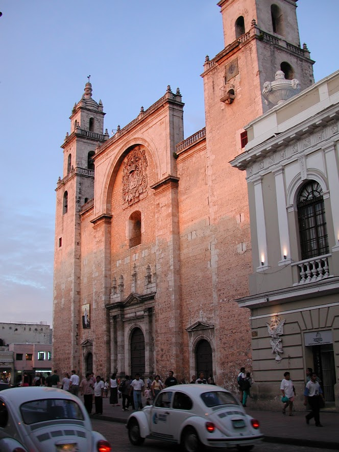 Façade of the Mérida cathedral in the evening light. Groups of pedestrians pass along the sidewalk in front as Volkswagen Beetles drive by.