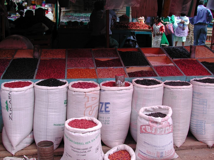 Dozens of varieties of dried beans in many colours arrayed for sale in bins and large sacks for sale at the market