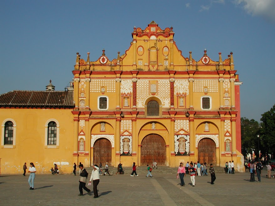 The bright yellow façade of a catheral faces the main plaza in San Cristóbal de las Casas. Pedestrials mill about the square in groups.