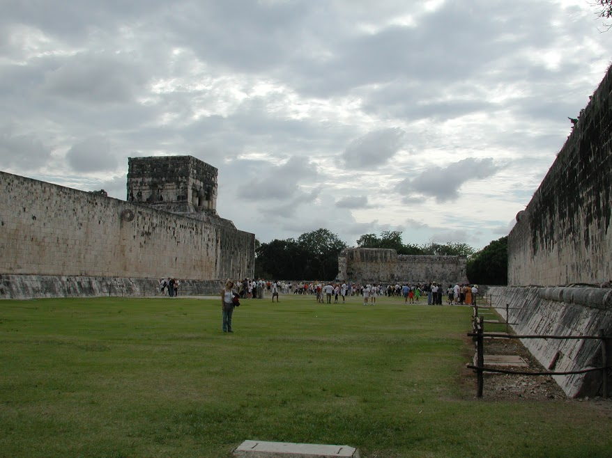The ball court at Chichen Itzá. Large, perfectly flat stone walls rise above the grass. Two stone hoops protrude, one from each wall, facing sideways. A crowd of people stands at the far end of the court.