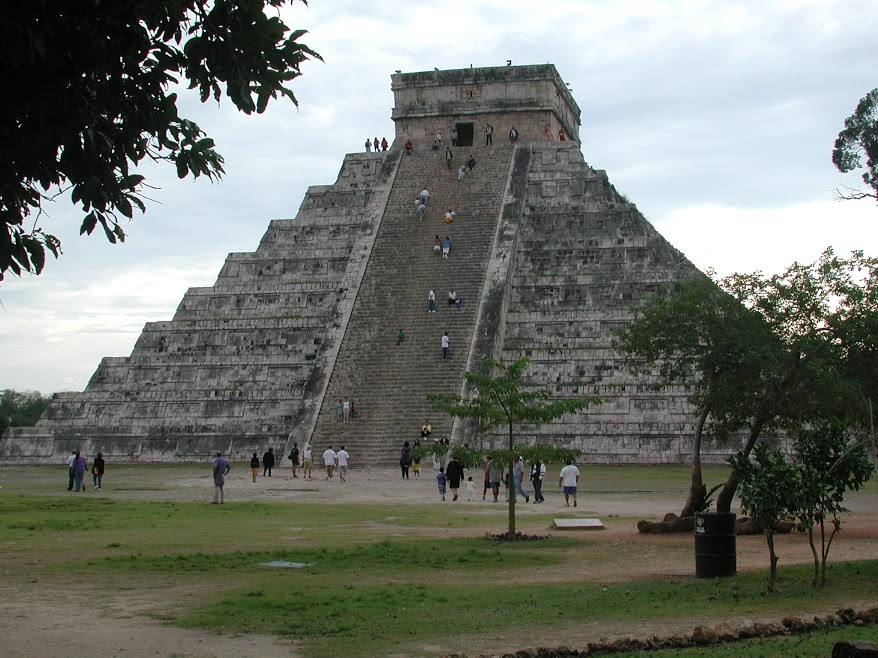 A view from the ground below the El Castillo pyramid at Chichen Itzá. Visitors climb the steep staircase leading up the centre of the face of the pyramid. A few people stand silhouetted at the top, looking down on the surrouding jungle.