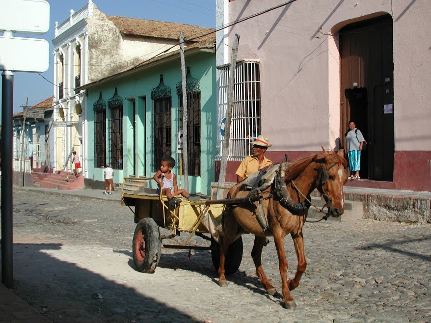 Horse-drawn cart driven by man and boy in Trinidad street